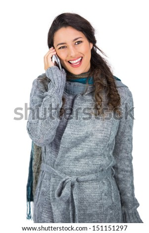 Smiling pretty brunette wearing winter clothes on the phone on white background - stock photo