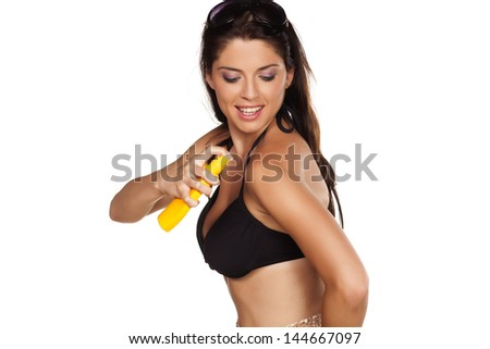 Smiling pretty girl applied a sunscreen spray - stock photo