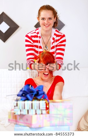 Smiling pretty girl covering girlfriends eyes for a surprise - stock photo