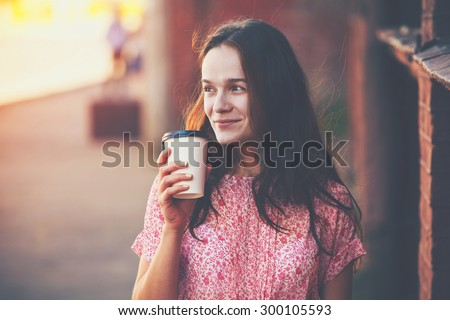 smiling pretty girl walking in street with morning coffee - stock photo