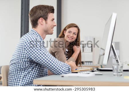 Smiling Pretty Office Worker Admiring her Handsome Colleague While Working at his Desk. - stock photo