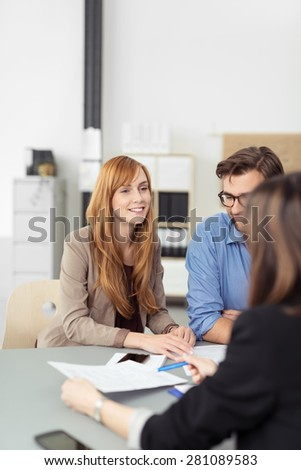 Smiling pretty redhead woman in a meeting at the office sitting at a table with her colleagues or team smiling - stock photo