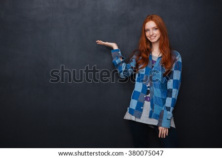 Smiling pretty redhead young woman standing and holding copyspace on palm over blackboard background - stock photo