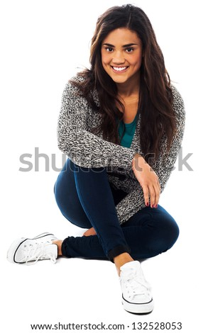 Smiling pretty relaxed girl seated on floor, indoor studio shot. - stock photo