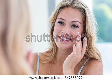 Smiling pretty woman applying cream on her face in bathroom - stock photo