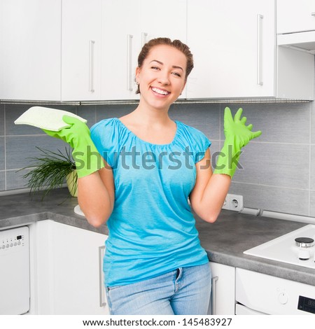 smiling pretty woman cleans the kitchen at home - stock photo