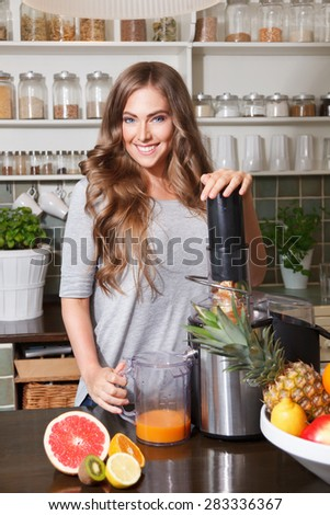 Smiling pretty woman making healthy fruit juice - stock photo