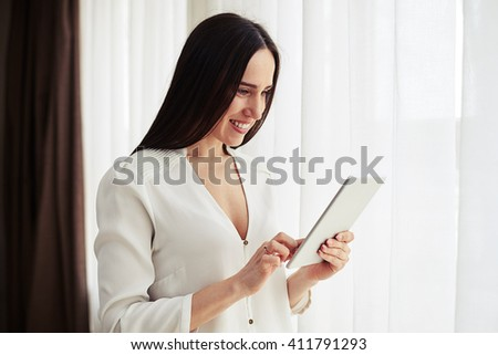 Smiling pretty woman standing and do something on the tablet  indoor - stock photo