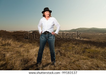 Smiling pretty woman with a hat middle aged enjoying outdoors. Feeling free standing in grassy dune landscape. Clear sunny spring day with blue sky. - stock photo
