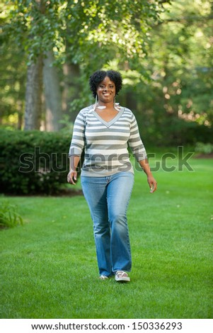 Smiling Pretty Young African American Female Walking Outdoor in Park - stock photo