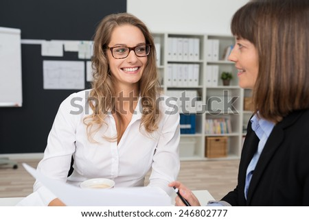 Smiling Pretty Young Office Woman with Blond Hair Talking to her Co-worker at her Worktable. - stock photo