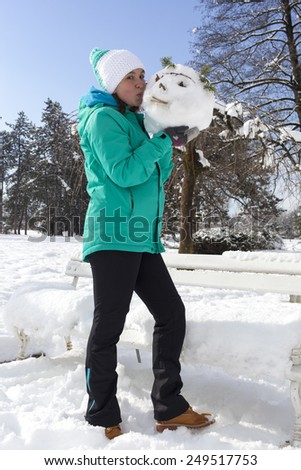 Smiling pretty young woman kissing a snowman head, outdoor on a sunny winter day - stock photo