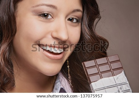 Smiling pretty young woman with chocolate bar - stock photo