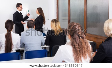 Smiling professor and professionals at extension business courses indoors - stock photo