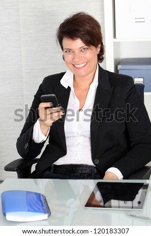 Smiling profile shot of a business woman sitting on her chair and posing with her cellphone. - stock photo