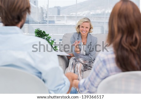 Smiling psychologist talking to a couple during therapy session - stock photo