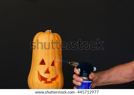 Smiling pumpkin Scary Halloween hand with flame - stock photo