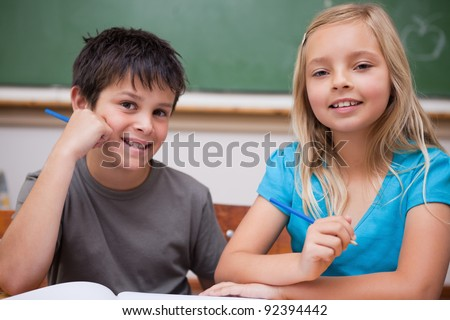 Smiling pupils working together in a classroom - stock photo