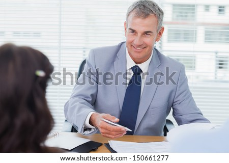 Smiling real estate agent completing contract with couple in bright office - stock photo