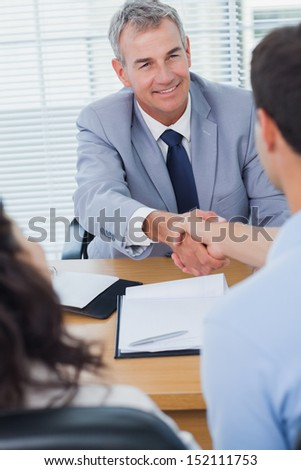 Smiling real estate agent shaking hands with his new buyer in bright office - stock photo