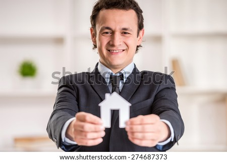 Smiling realtor man is holding a model of home. - stock photo