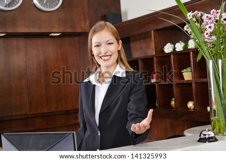 Smiling receptionist behind desk in hotel offers welcome to guest - stock photo