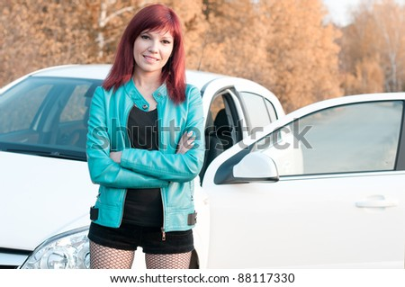 Smiling red-haired young woman standing by her car on an autumn road - stock photo