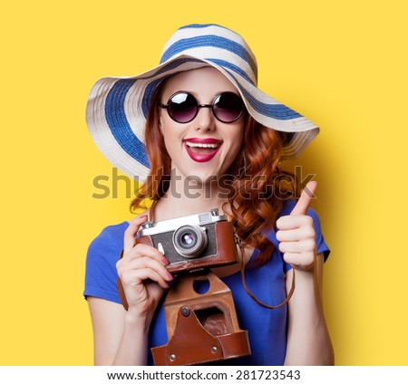Smiling redhead girl in blue dress and hat  with camera on yellow background. - stock photo