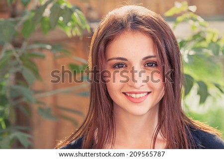 Smiling redhead teen. Front view closeup image of a  smiling teenage girl outdoors against old wood plank background with leaves - stock photo