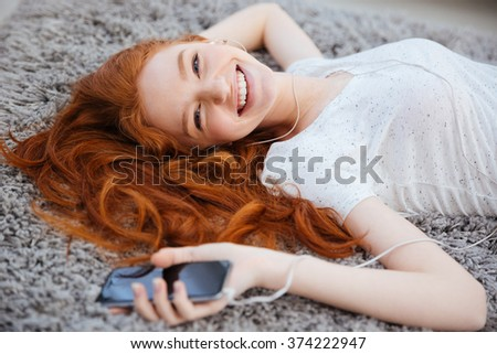 Smiling redhead woman with headphones lying on the carpet and listening music on smartphone at home - stock photo