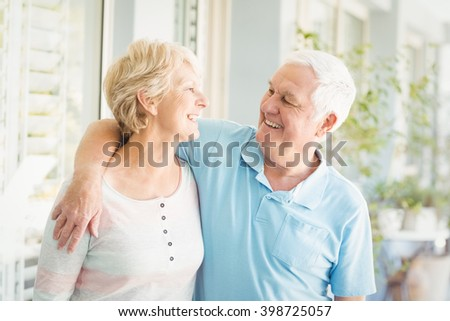Smiling romantic senior couple by wall at home - stock photo