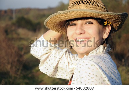 Smiling rural girl with straw hat - stock photo