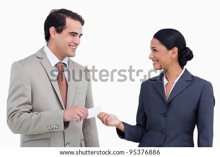 Smiling sales partner exchanging business cards against a white background - stock photo