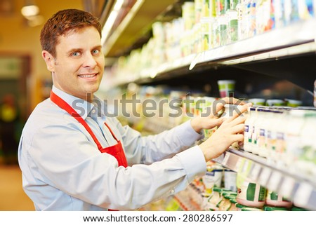 Smiling salesman organizing dairy products in supermarket shelf - stock photo