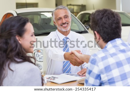 Smiling salesman shaking a customer hand at new car showroom - stock photo
