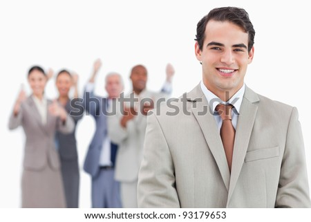 Smiling salesman with cheering team behind him against a white background - stock photo