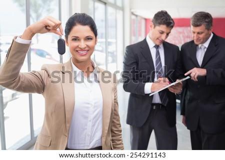 Smiling saleswoman holding a customer car key at new car showroom - stock photo