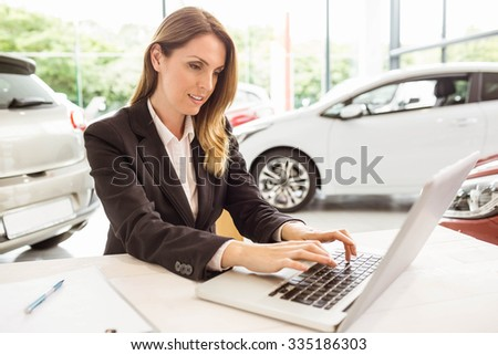 Smiling saleswoman typing on her laptop at new car showroom - stock photo