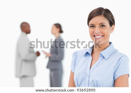 Smiling saleswoman with talking colleagues behind her against a white background - stock photo