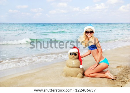 Smiling sandy snowman in red santa hat and attractive blonde woman on the sea beach. Holiday concept can be used for New Year and Christmas Cards - stock photo