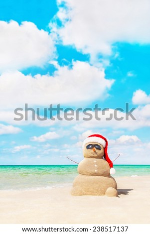 Smiling sandy snowman in red santa hat at tropical beach. New Years and Christmas holidays in hot countries concept - stock photo