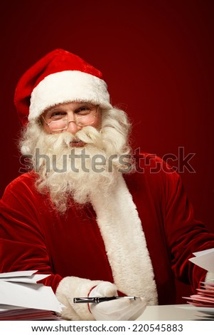 Smiling Santa Claus with pen looking at camera while answering Christmas letters - stock photo