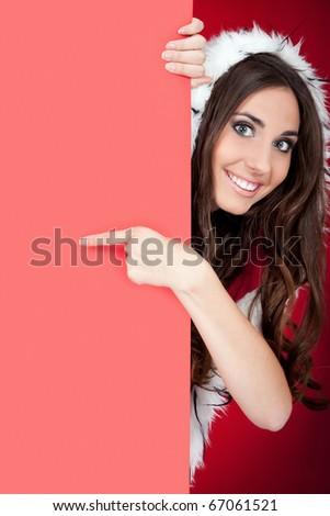 smiling santa girl behind blank board pointing - stock photo