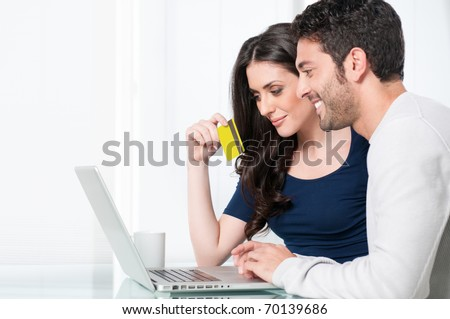 Smiling satisfied couple buying online with credit card at home - stock photo