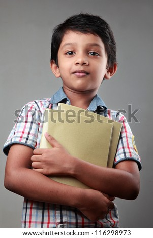 Smiling school boy with note books in his hands - stock photo