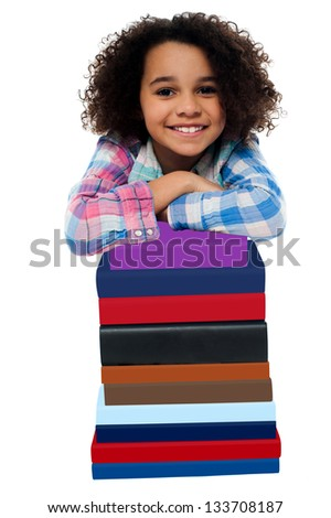 Smiling school girl leaning over pile of colorful books. - stock photo