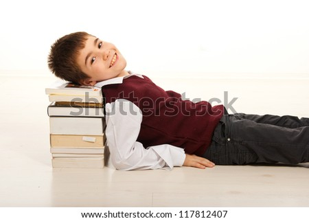 Smiling schoolboy resting head on stack of books and laying on floor home - stock photo