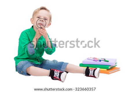 smiling schoolboy sitting on a white background, surrounded by books and holding a magnifying glass, picture with depth of field - stock photo