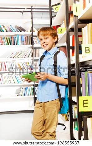Smiling schoolboy stands and holds books - stock photo