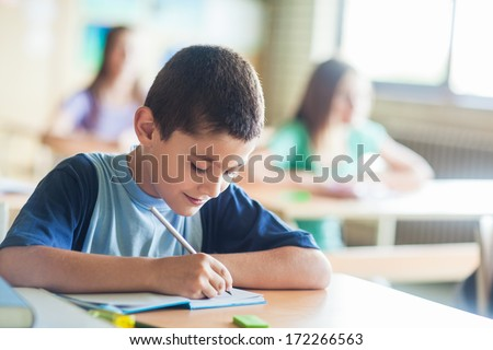 Smiling schoolboy writing notes in class. - stock photo